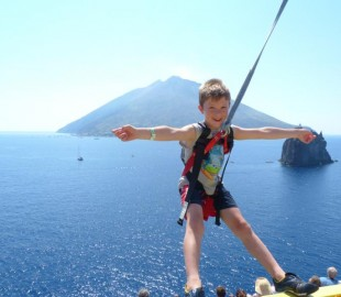 My Son Aaron on the ropes course on Carnival Magic as we pass the volcanic island of Stromboli