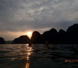 The boat slips between the islands of halong bay as the sun sets