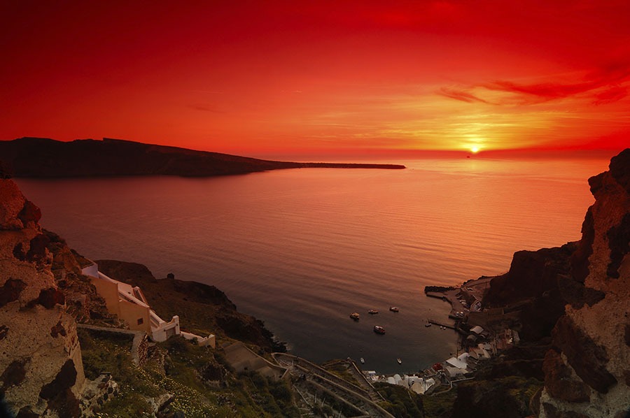 Image shows a spectacular sunset in the village of Oia, Santorini, Greece