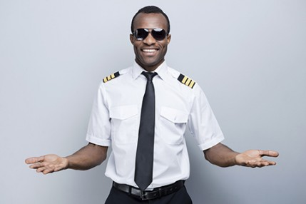 Welcome on board! Happy African pilot in uniform gesturing welco