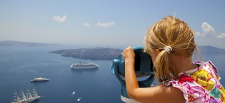 Girl looking at cruise ships with binoculars in Thira, Santorini, Greece
