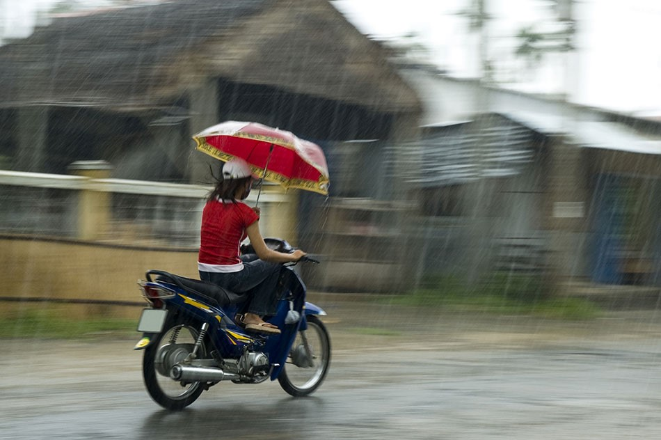 Vietnamese woman Umberlla on a scooter