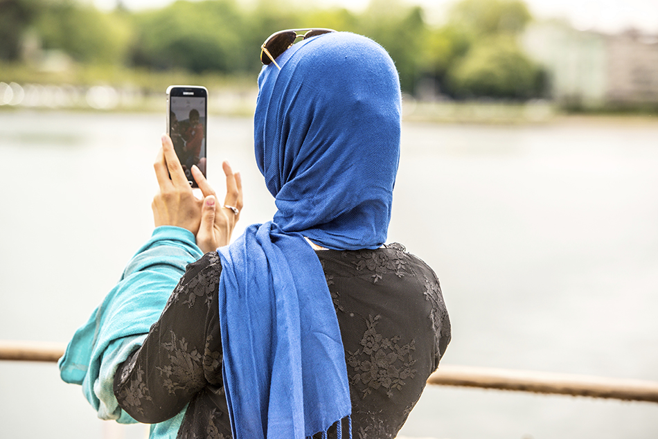 Woman photographing her family with mobile phone