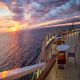 Sunset on a cruise ship with tables and chairs.  Carefully shot scene making sure that no copyrighted ship design is depicted.