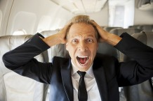 Fear of flight. Shocked mature businessman touching his head wit