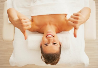 Portrait of happy young woman laying on massage table and showing thumbs up
