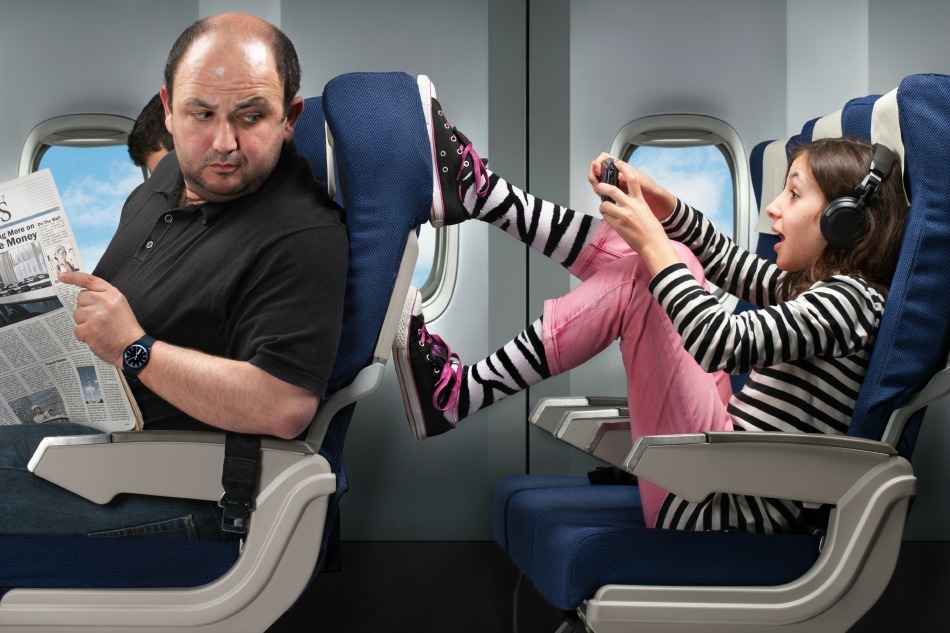 child kicking mans seat on plane