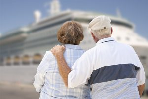 Senior Couple On Shore Facing and Looking at Docked Cruise Ship.