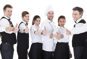 Waiters and waitresses showing thumbs up sign.