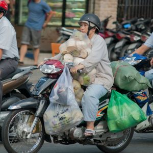 Old vietmanese lady carrying shopping on a scooter