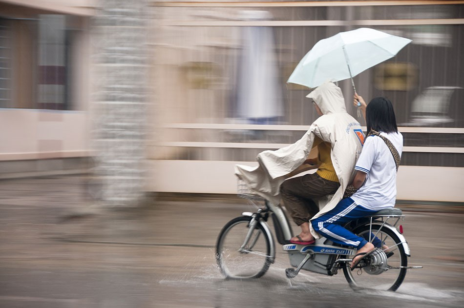 Vietnamese couple with Umberella and poncho on a scooter