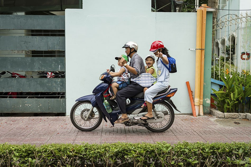 family riding a scooter on a path in vietnam