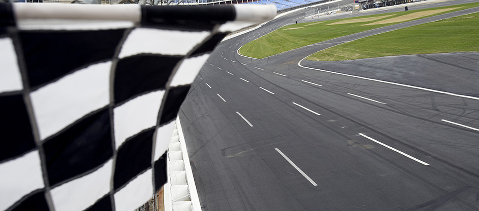 view from finish line with checkered flag waving at the race track.