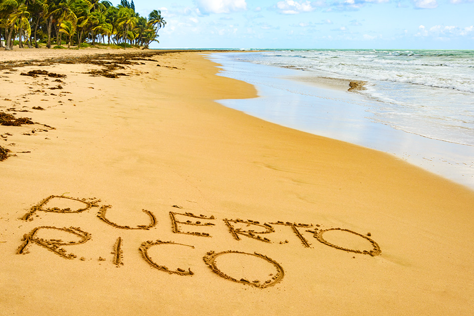 Puerto Rico written on one of its beautiful beaches with turqouise waters and cloudy skies
