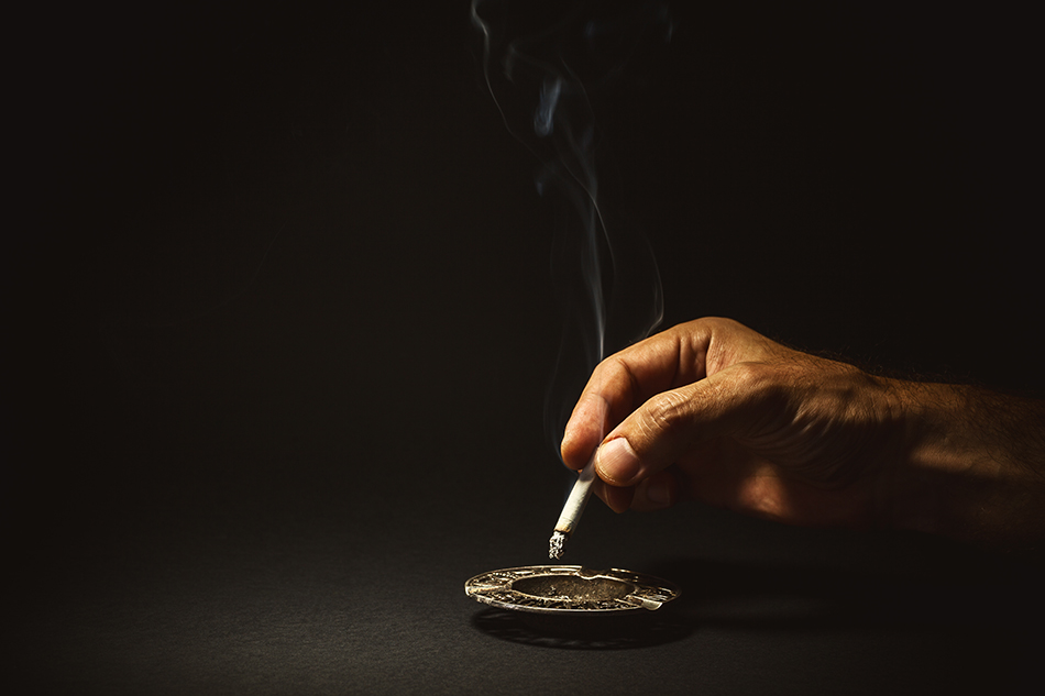 Conceptual composition about quit smoking, man's hand extinguishes a cigar.