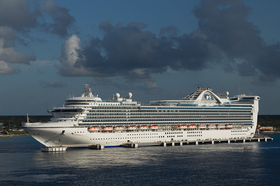 Cozumel, Mexico - February 6, 2014: Caribbean Princess , one of the two biggest cruise ships in the world, docked in Cozumel, Mexico. Sunny afternoon. Passengers are still off the ship enjoying local cousine, beautiful beaches and exploring Cozumel Island